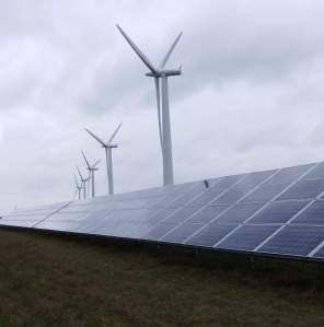 Ground based solar panels with wind turbines